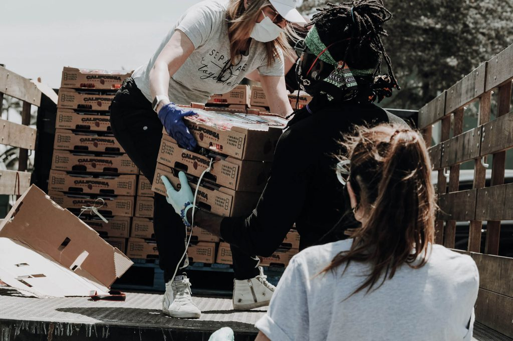 Three women loading boxes of fruit into a truck bed