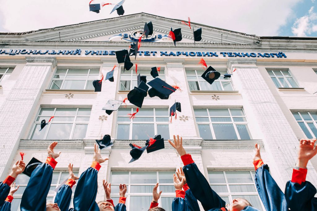 Graduation caps being thrown into the air in front of a school building