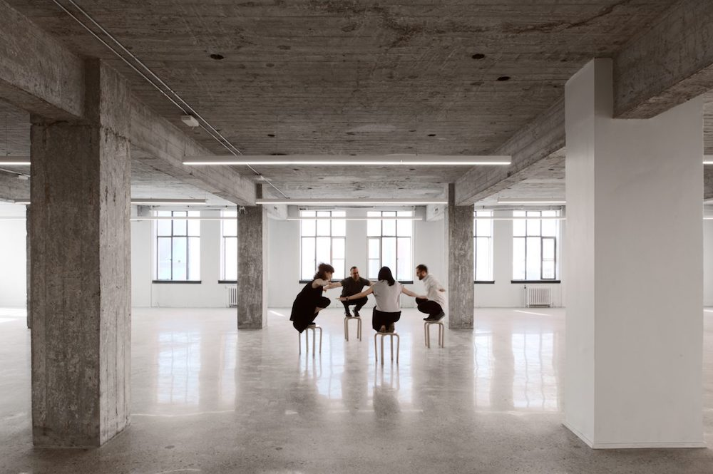 Giaimo team members in the middle of a concrete room, huddled in a circle.